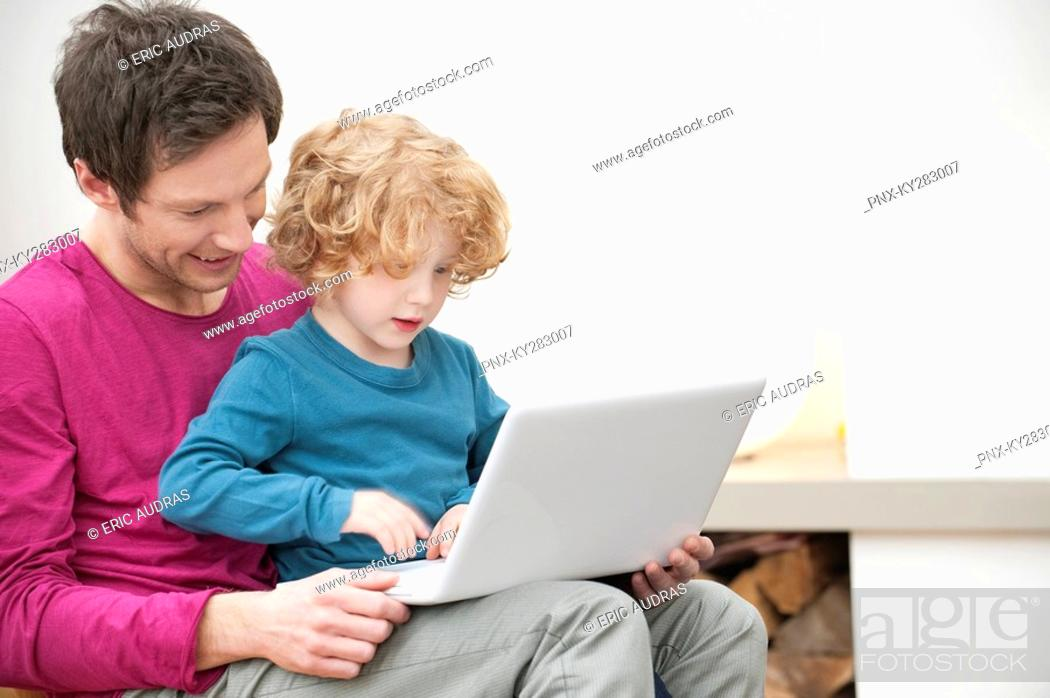 Stock Photo: Close-up of a man assisting his son in using a laptop.