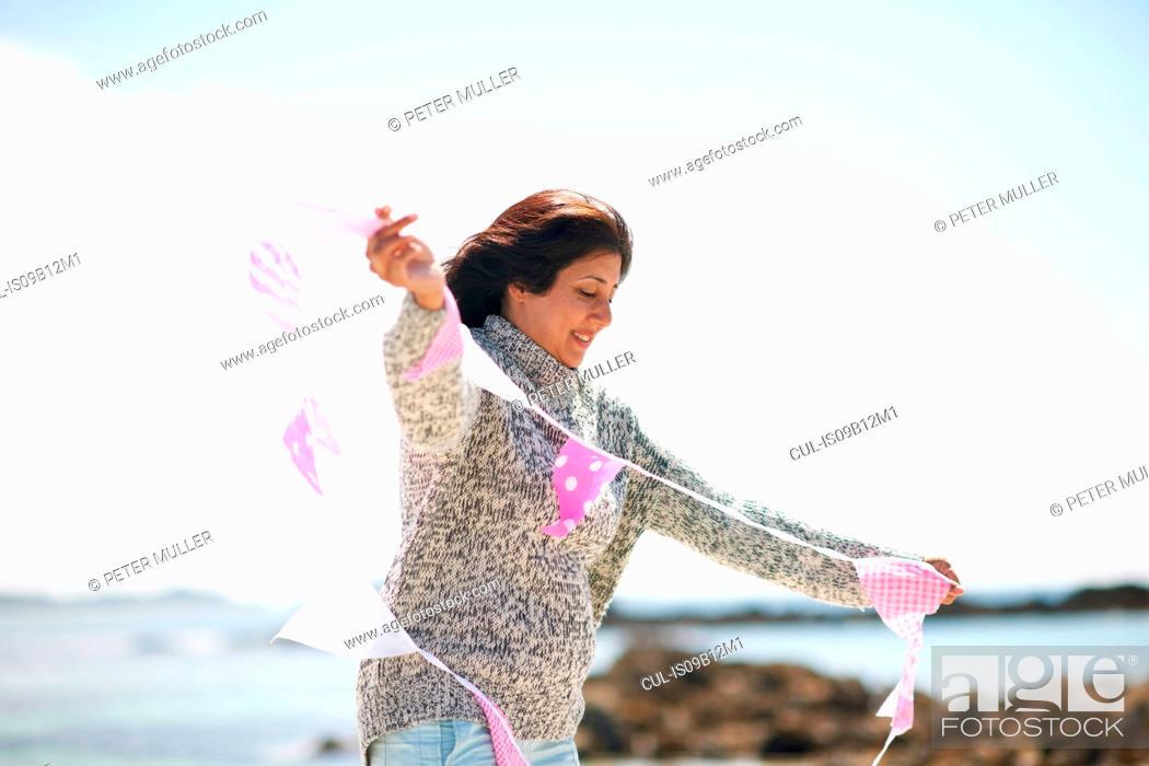 Stock Photo: Woman at coast holding bunting.