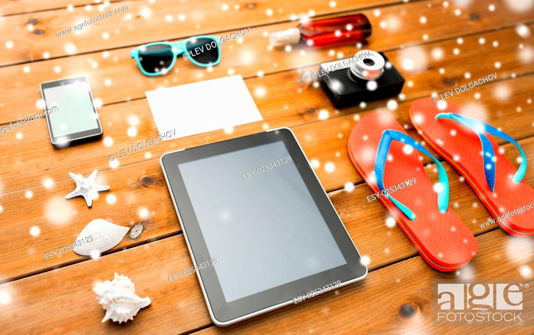 Stock Photo: vacation, tourism, winter holidays, technology and travel concept - tablet pc computer and beach stuff over snow.