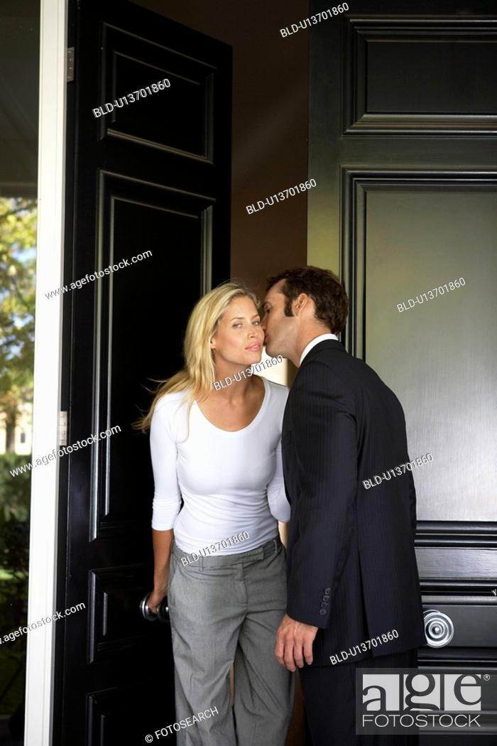 Stock Photo: Husband kissing wife before leaving for work.