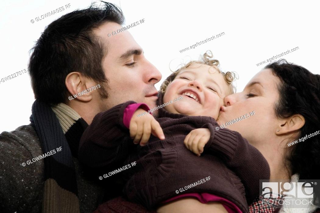 Stock Photo: Close-up of a couple kissing their daughter.