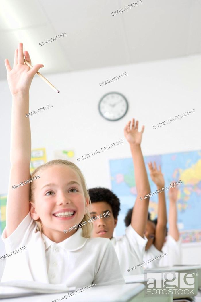 Stock Photo: Multi-ethnic children raising hands in class.