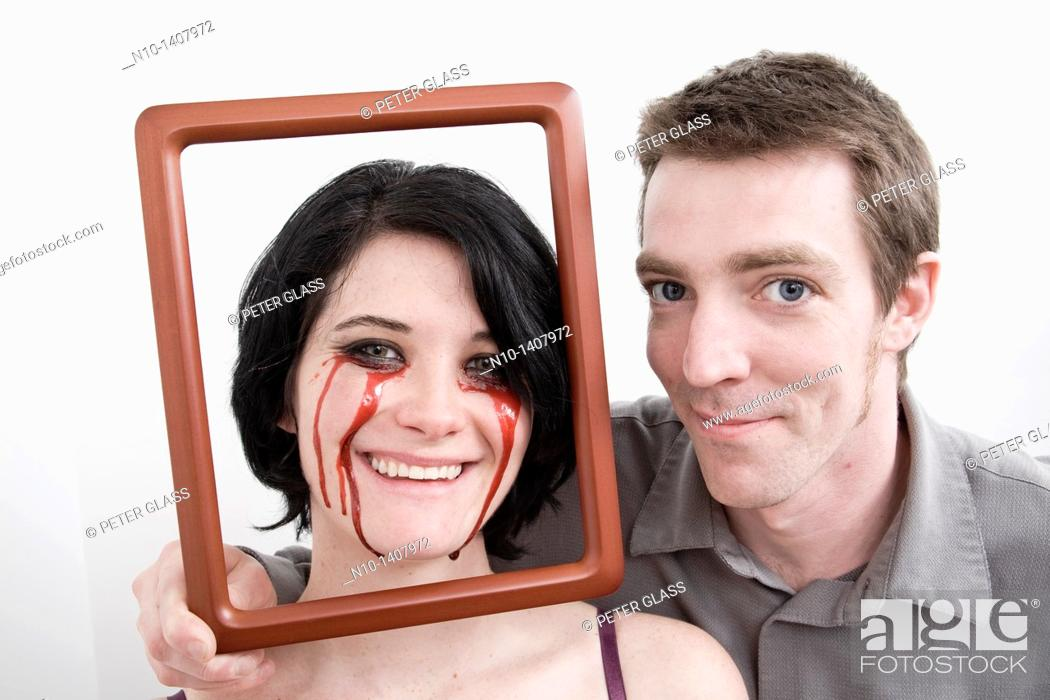 Stock Photo: Man holding frame in front of wife, who has blood dripping from her eyes.