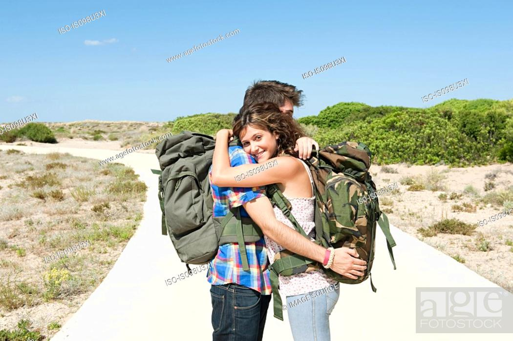 Stock Photo: Young couple wearing backpacks embracing.