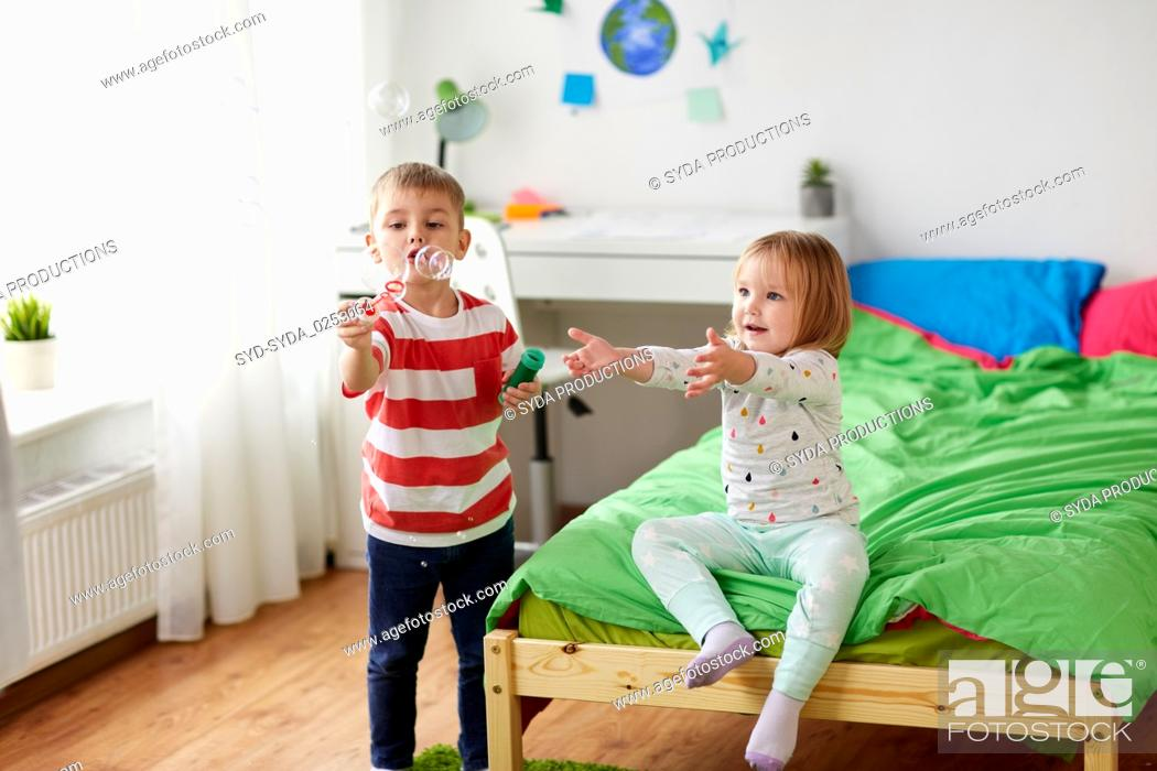 Stock Photo: kids blowing soap bubbles and playing at home.