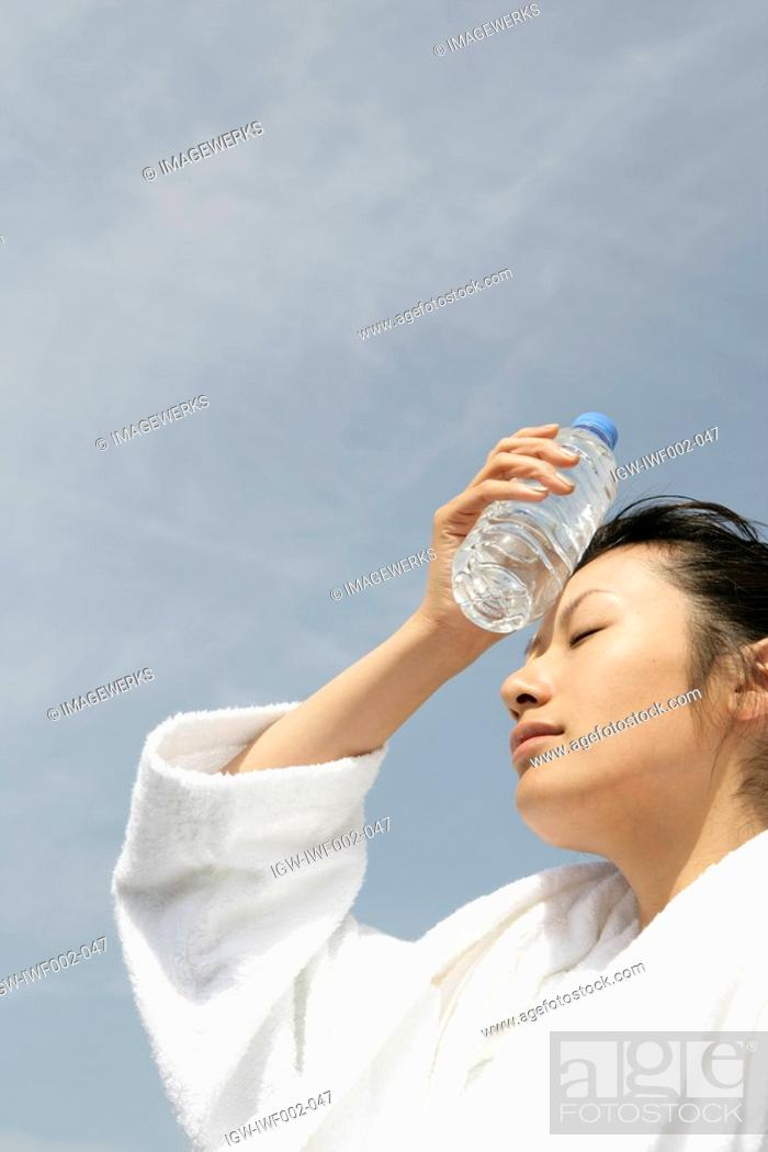 Stock Photo: A woman in bathrobe placing a bottle of water on her forehead.