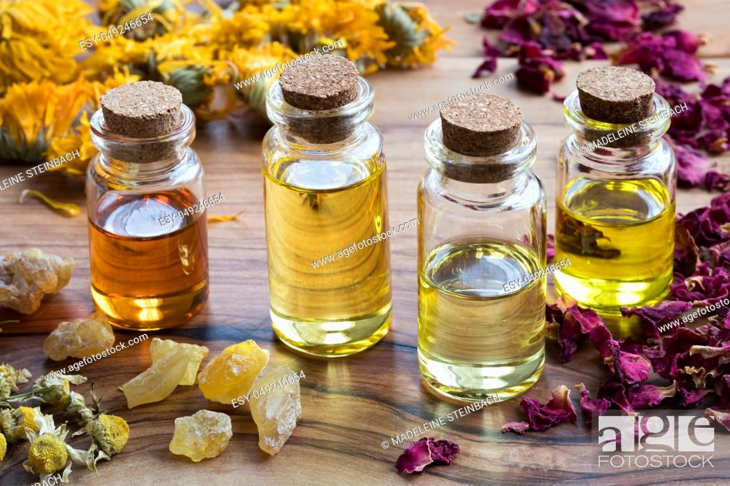 Stock Photo: Bottles of essential oil with dried rose petals, chamomile, calendula and frankincense on a wooden table.