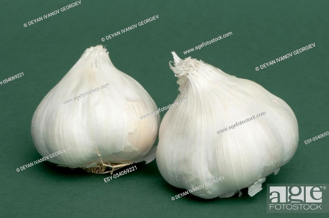 Stock Photo: Whole heads of garlic on green background.