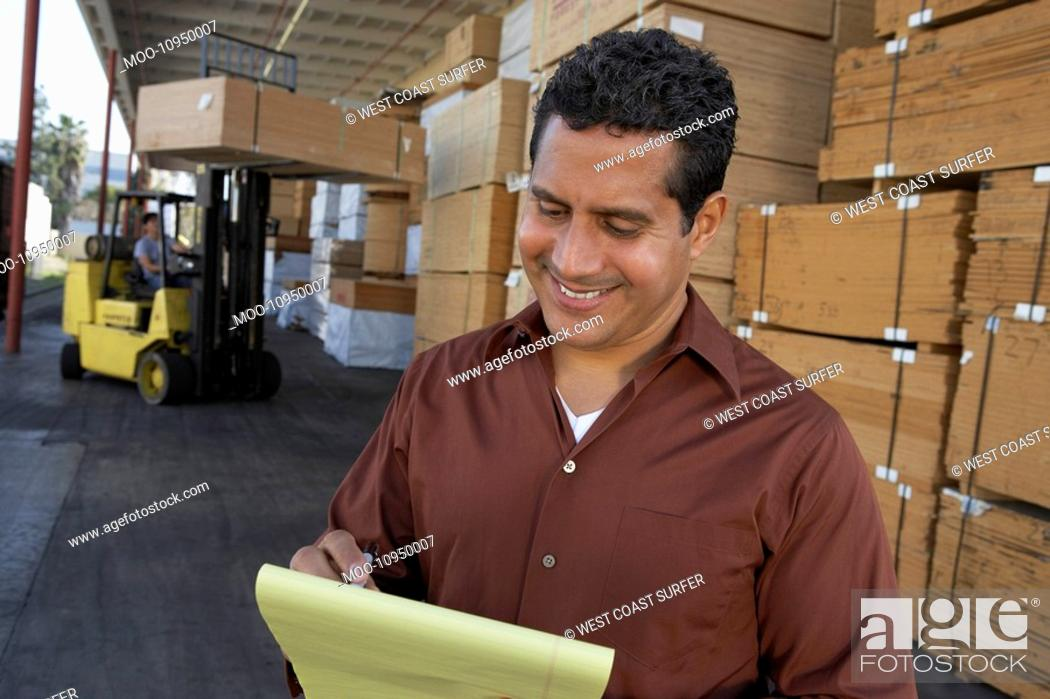 Stock Photo: Warehouse Worker in front of man working with forklift.