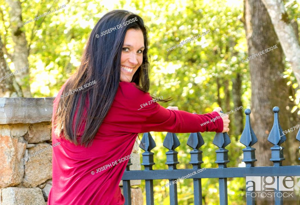 Stock Photo: A smiling 38 year old brunette woman looking over her shoulder, dressed in jeans outdoors.
