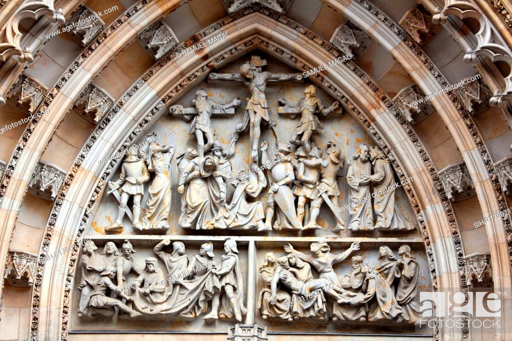 Stock Photo: Tympanum Reliefs Above the Bronze Door of the central portal in the St. Vitus Cathedral's western facade, depicting The Crucifixion and a game of dice in order.