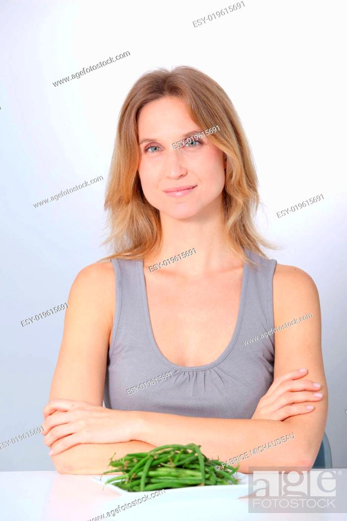Stock Photo: Woman in front of plate of green beans.