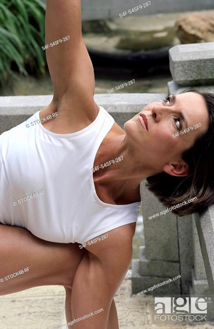 Stock Photo: Darkhaired Woman stretching her Arm up - Physical Exercise - Yoga - Terrace.