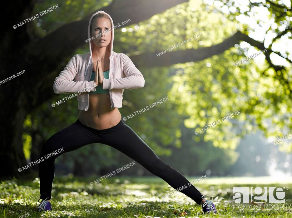 Stock Photo: Young woman making stretching exercise on a meadow.