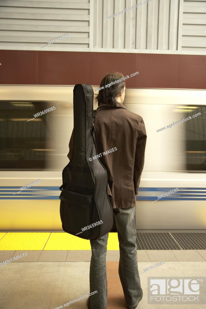 Stock Photo: Rear view of man with guitar waiting for train.