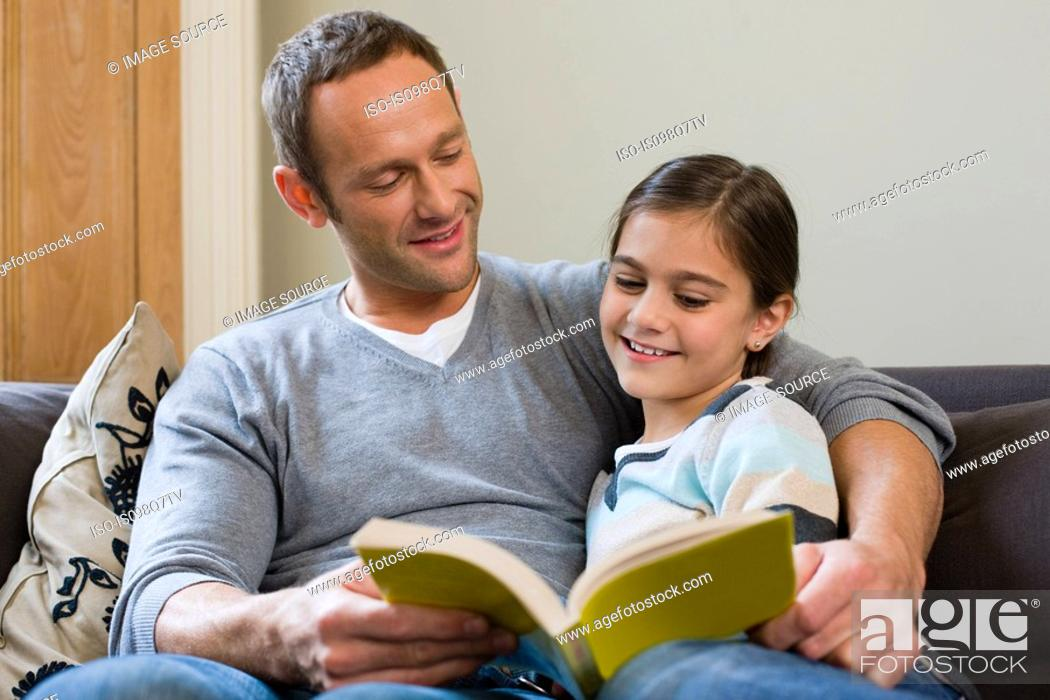 Stock Photo: Father and daughter reading a book together.
