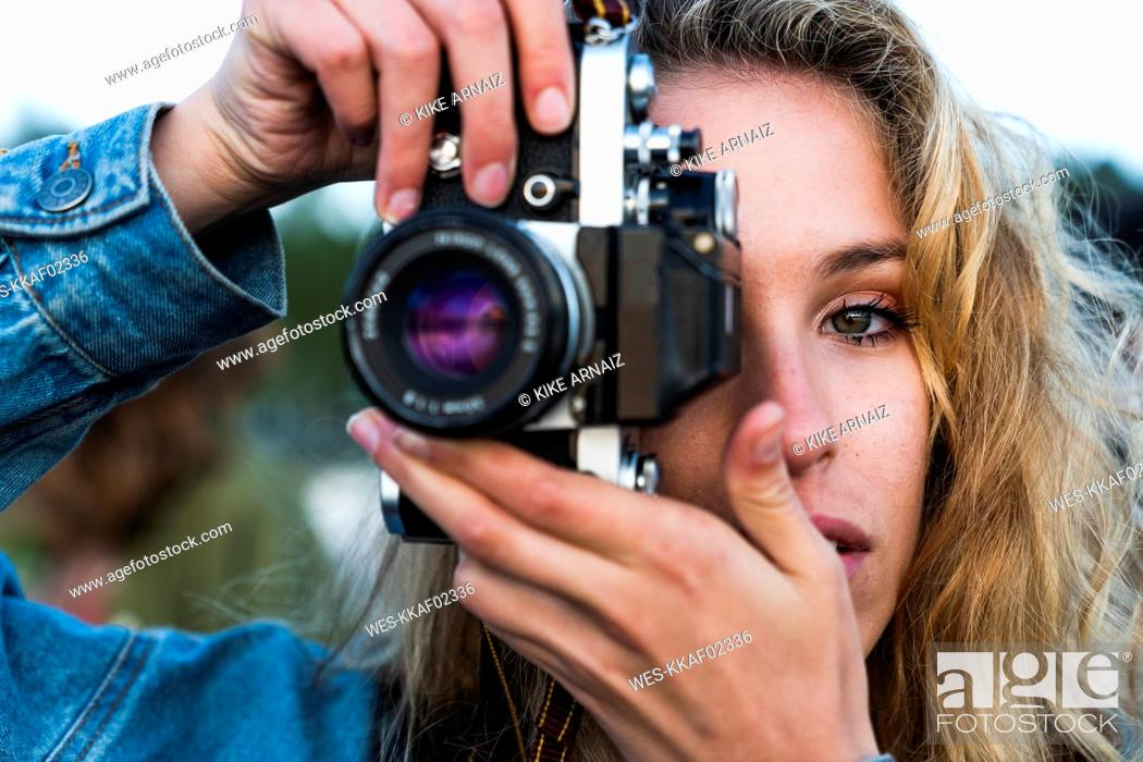 Stock Photo: Close-up of beautiful blond young woman taking a picture with a camera.
