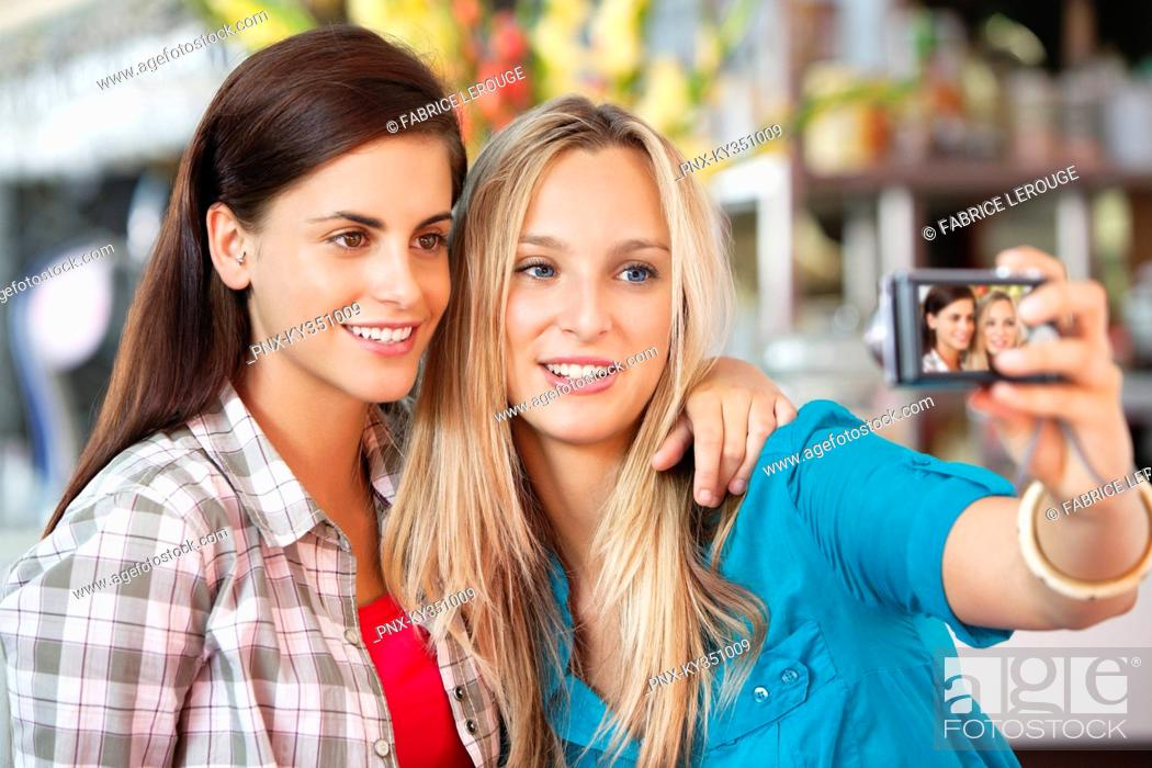 Stock Photo: Female friends taking a picture of themselves with a camera.