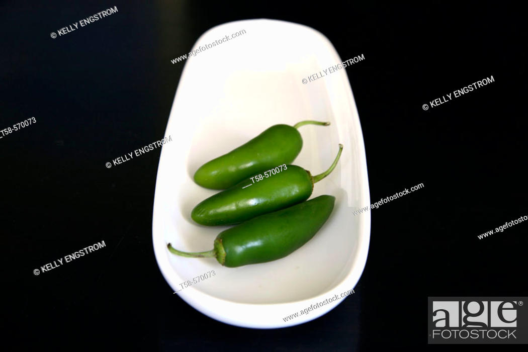 Stock Photo: Studio shot of chilli peppers on white tray, black background.