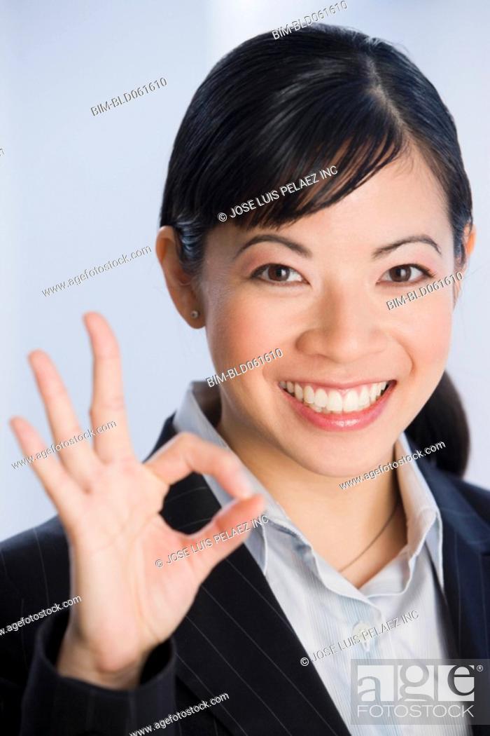 Stock Photo: Asian businesswoman making okay hand gesture.
