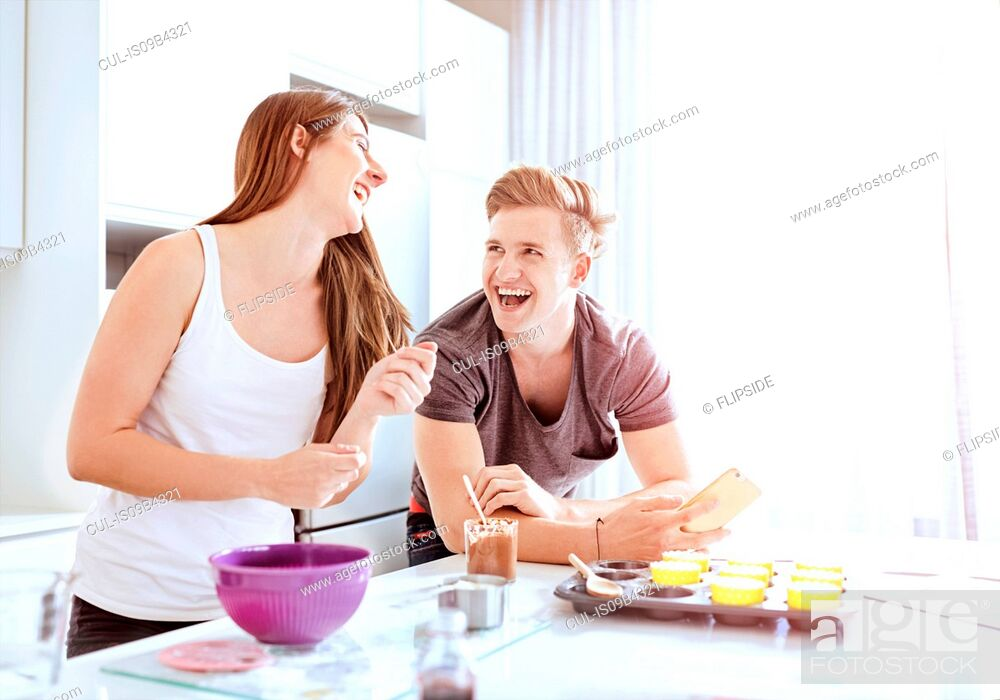 Stock Photo: Couple preparing food in kitchen.