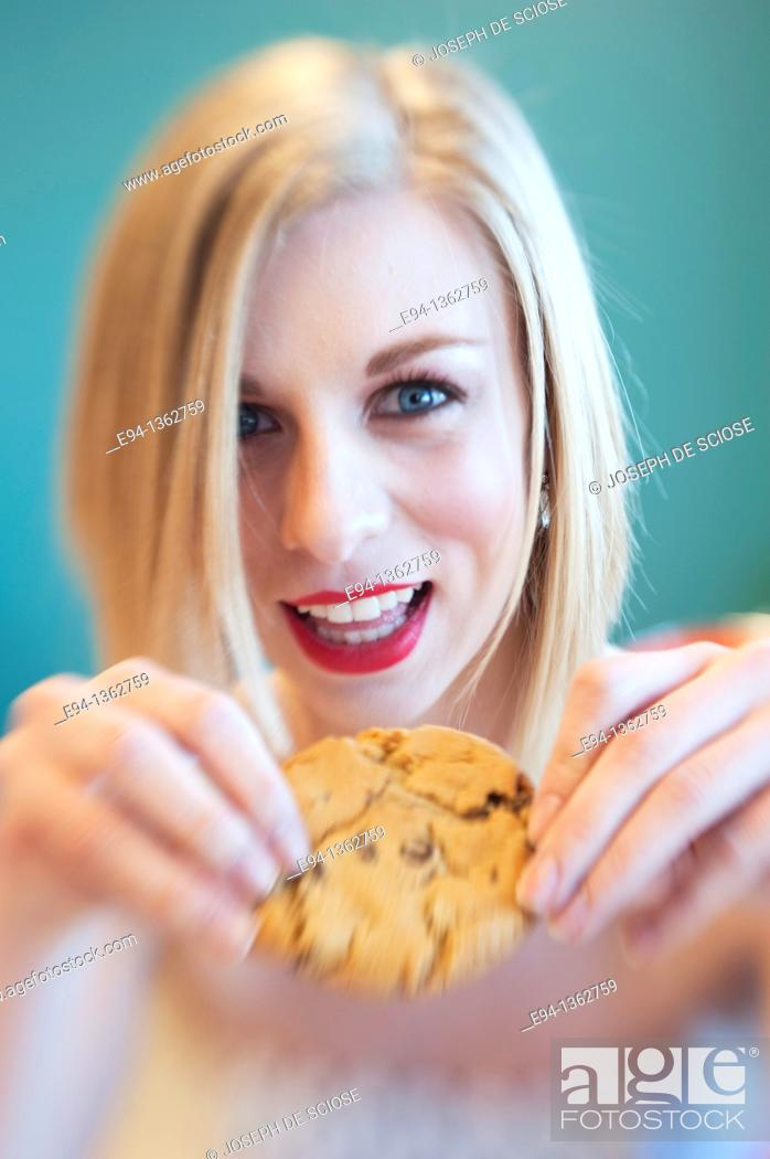Stock Photo: 19 year old blond woman holding a chocolate cookie.
