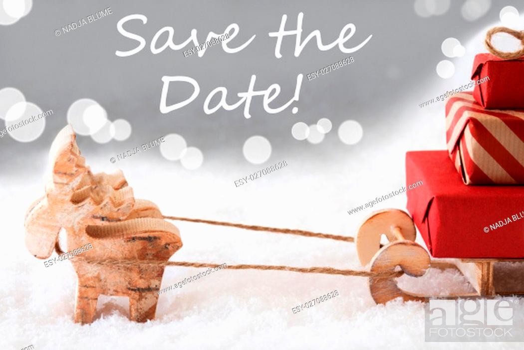 Stock Photo: English Text Save The Date. Moose Is Drawing A Sled With Red Gifts Or Presents In Snow. Christmas Card For Seasons Greetings.
