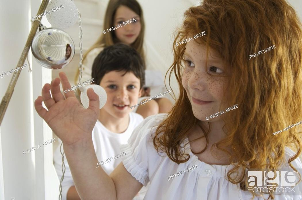 Stock Photo: Portrait of a little girl looking a Christmas ball on a branch, brother and sister in background, indoors.