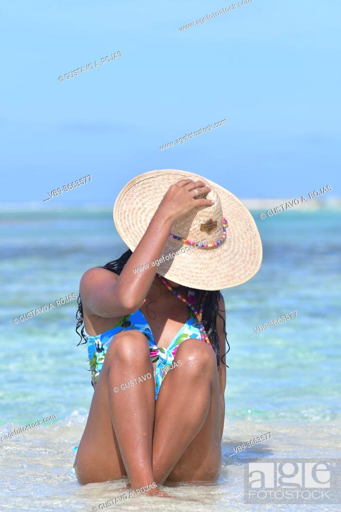Photo de stock: Hispanic woman siting on sand beach laughing with close eyes and splash water. Los Roques Venezuela.