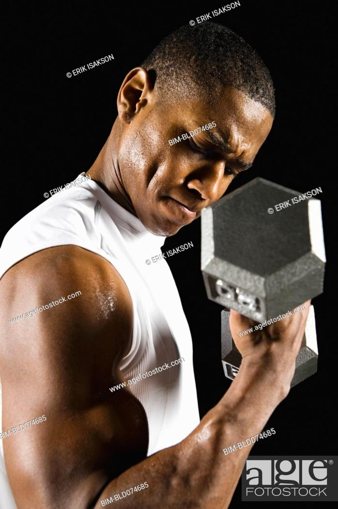 Stock Photo: African man doing biceps curl with dumbbell.