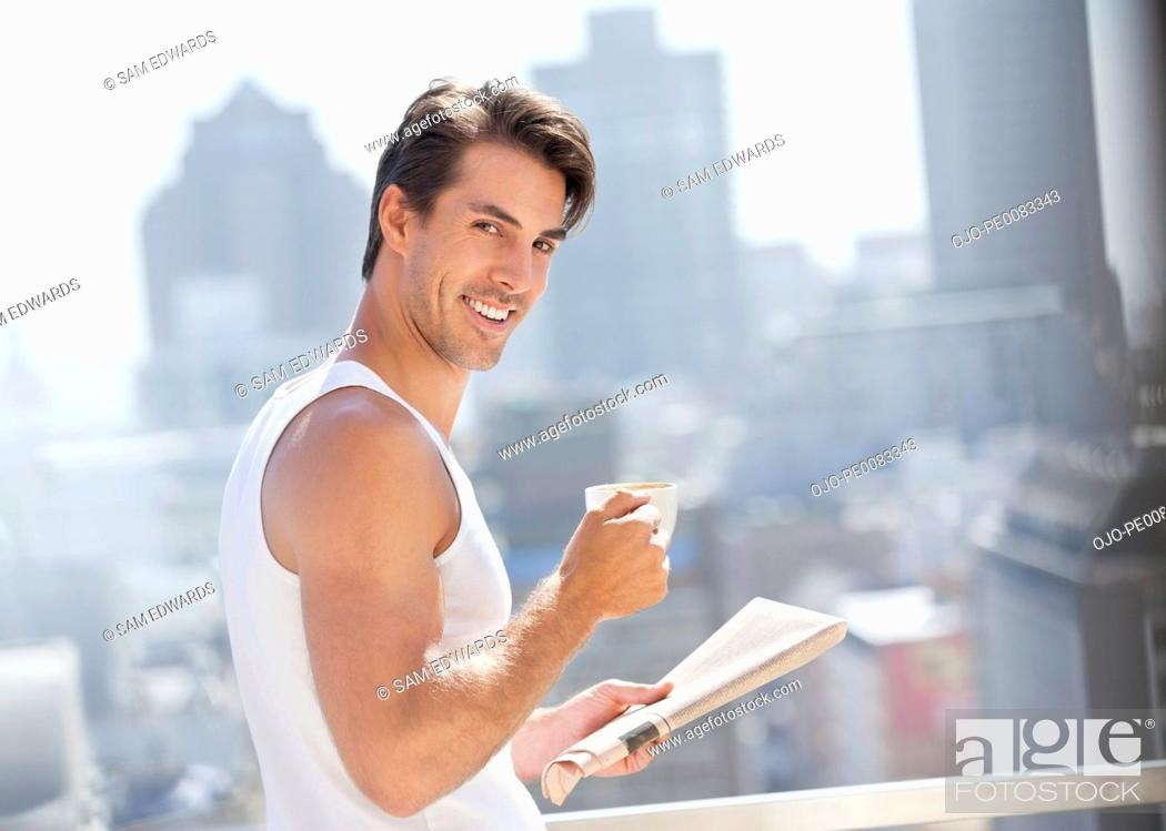 Stock Photo: Portrait of smiling man drinking coffee and reading newspaper on urban balcony.