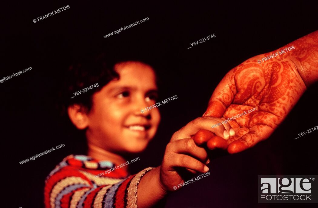Stock Photo: Daughter holding the hand of her mother. Rajasthan, India. The mother has a henna design on her hand.