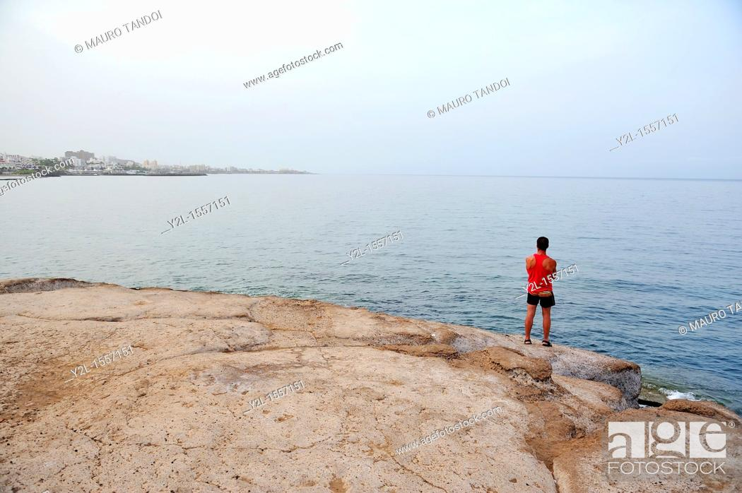 Stock Photo: A young man watching the sun rise behing the Fanabe Beach skyline across the bay  Tenerife, Spain.