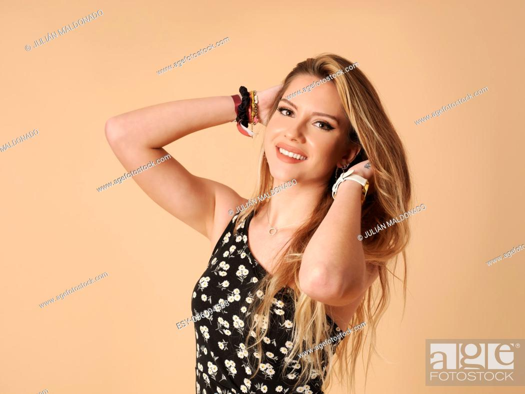 Stock Photo: Beautiful young woman with cheerful and friendly fitness holding her hair.