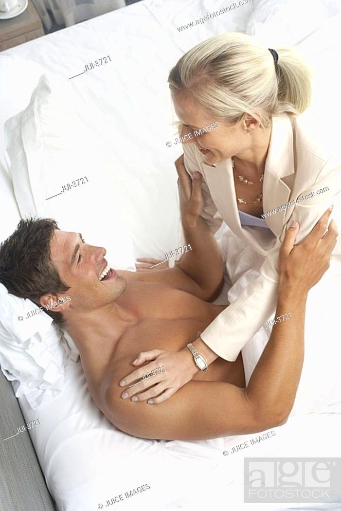 Stock Photo: Couple playfighting in bed, woman sitting on top of man, smiling, side view, elevated view.