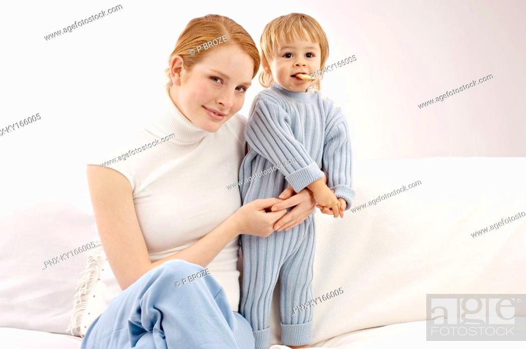 Stock Photo: Portrait of a young woman sitting on a couch with her son.