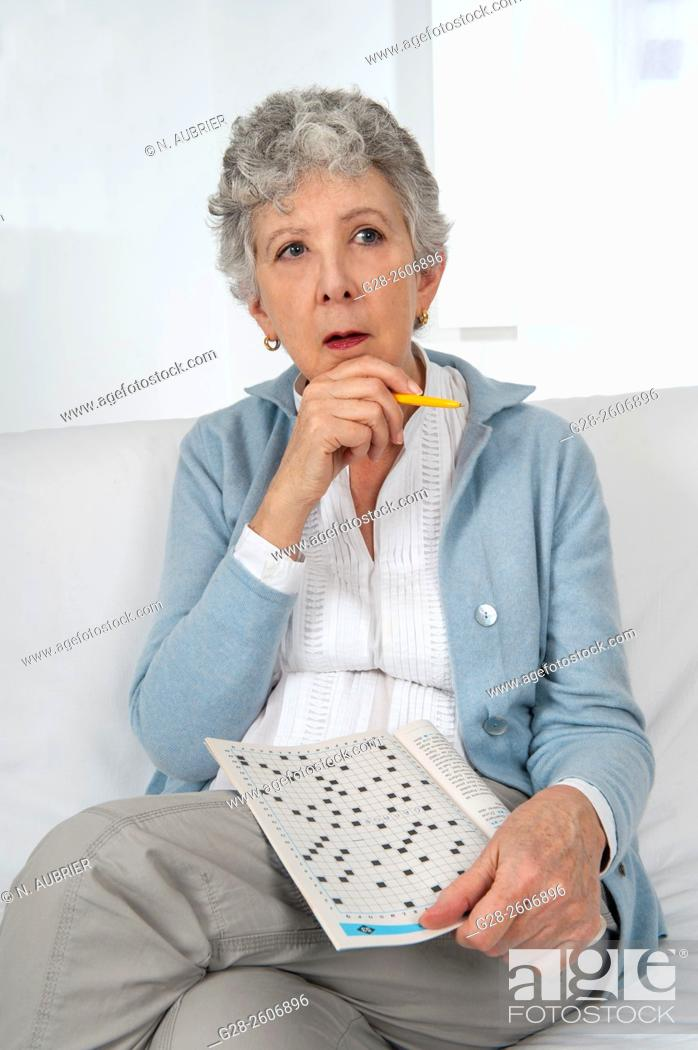 Stock Photo: Senior woman with grey hair, busy making a crossword, thoughtful, pen in hand.