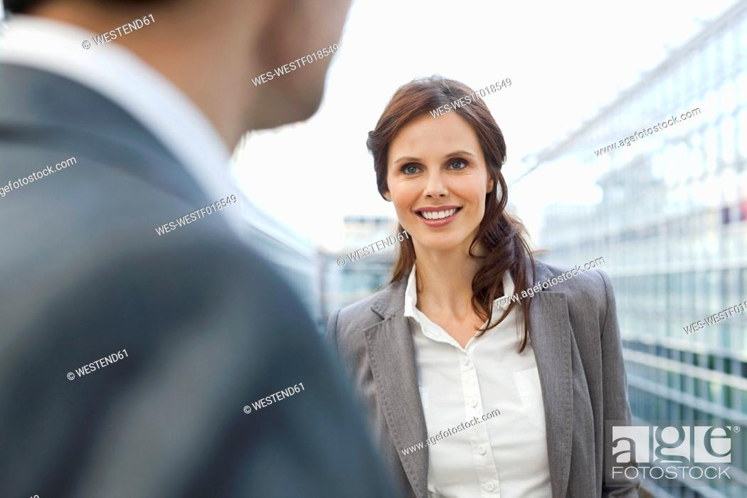Stock Photo: Germany, Leipzig, Businesswoman smiling, businessman in foreground.