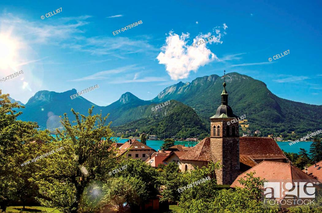 Stock Photo: View of houses and belfry with blue sky mountains landscape, in the village of Talloires. A lovely village next to the Lake of Annecy.