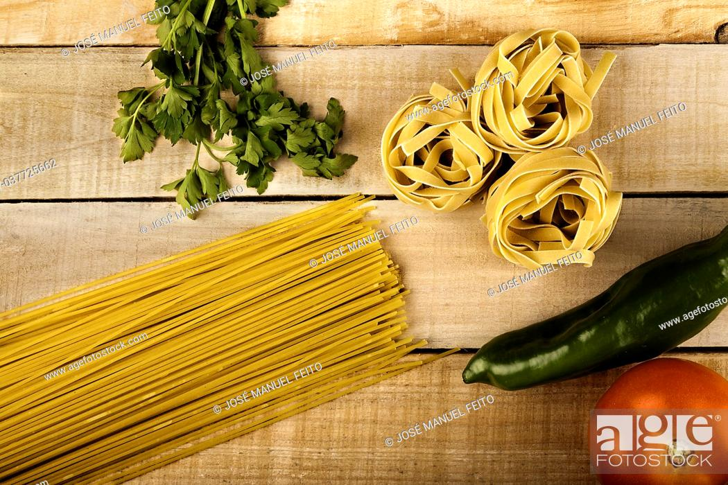 Stock Photo: Spaghetti, tomato, pepper, fettuccine and parsley on wood.