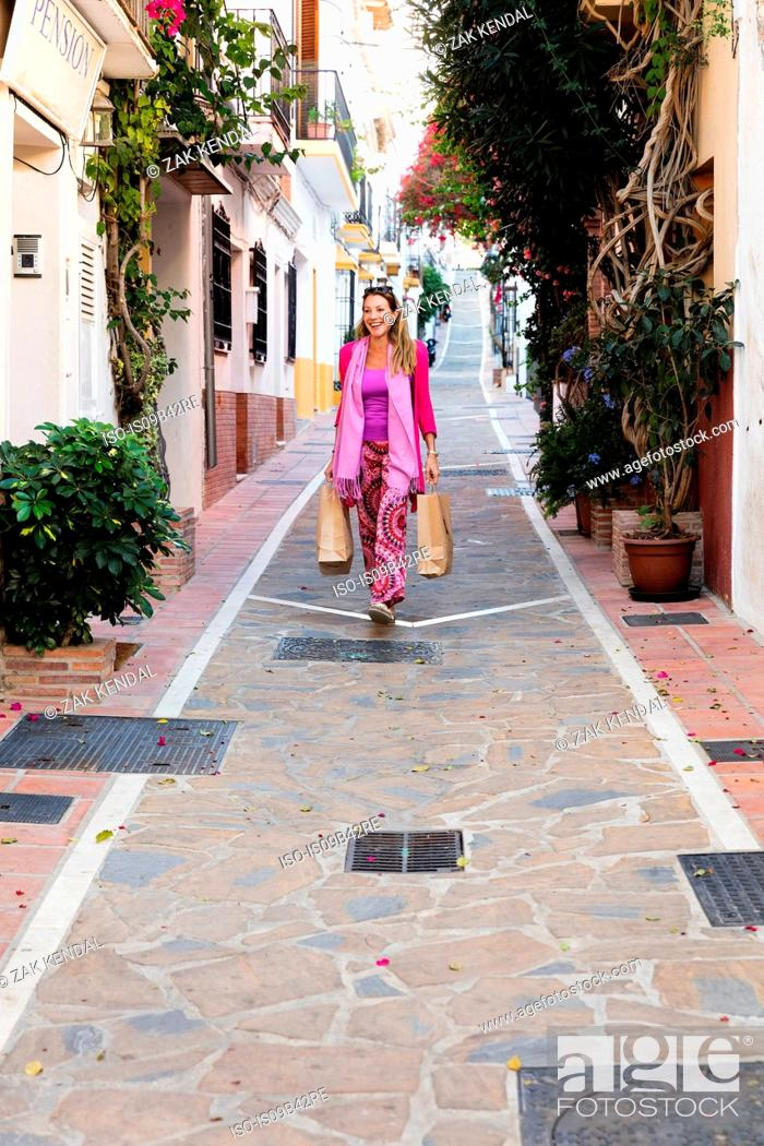 Stock Photo: Mature female tourist strolling down alley with shopping bags, Marbella, Spain.