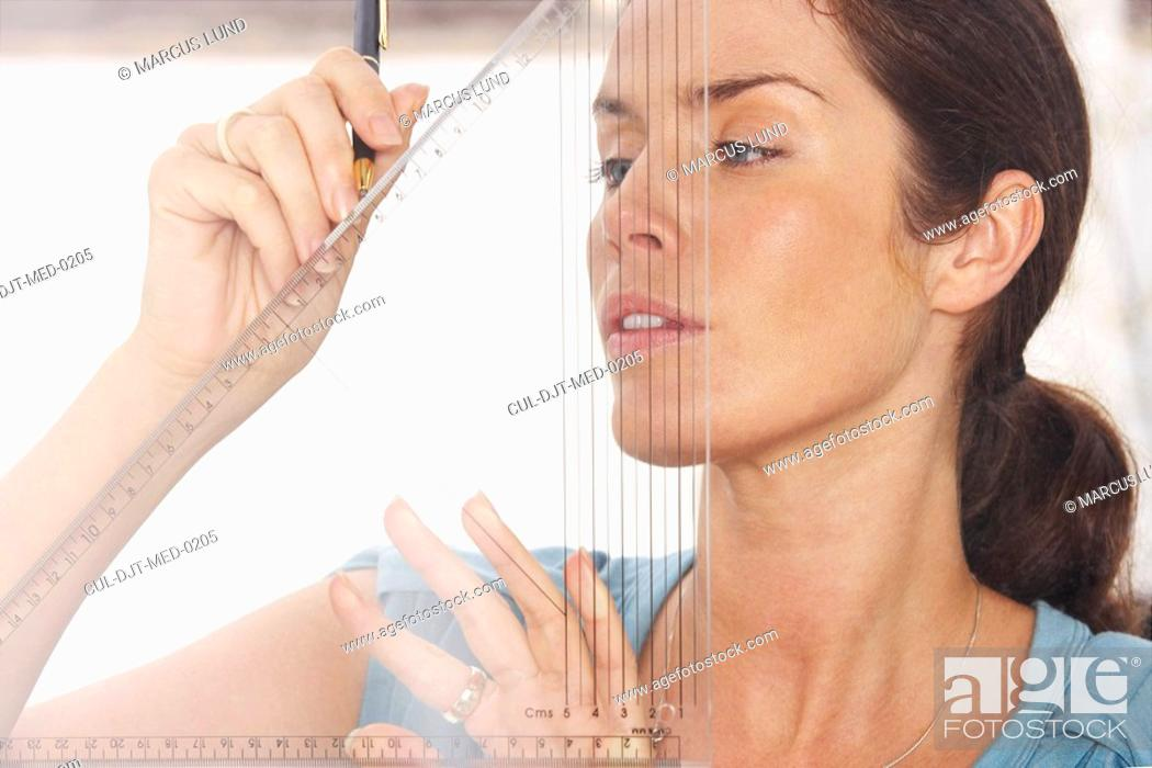 Stock Photo: Close-Up portrait of woman through window using graphic drawing equipment.