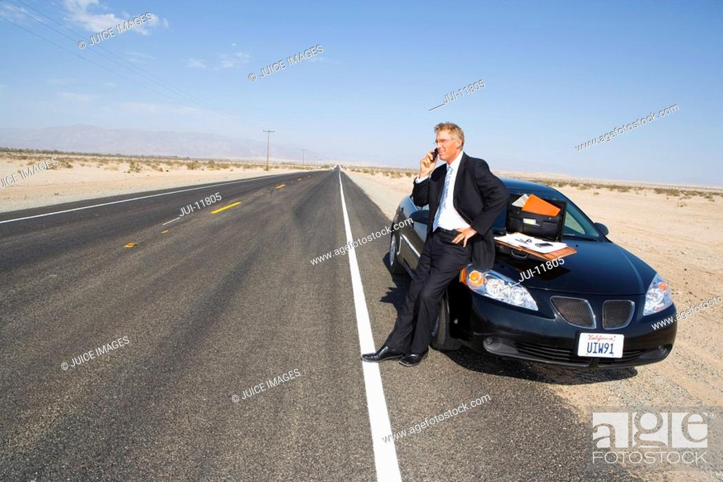 Stock Photo: Businessman using mobile phone by car on side of road in desert, paperwork on bonnet of car.