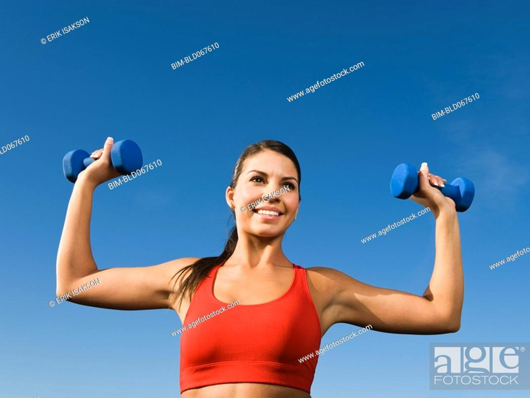Stock Photo: Native American woman lifting hand weights.