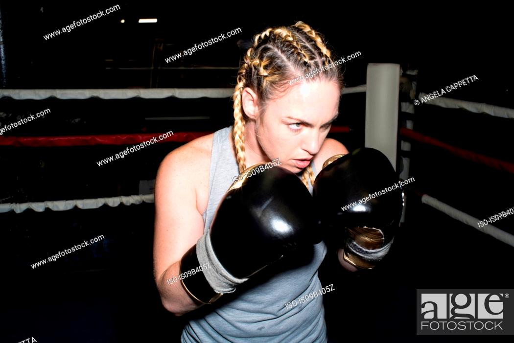 Stock Photo: Female boxer poised for sparring in boxing ring.