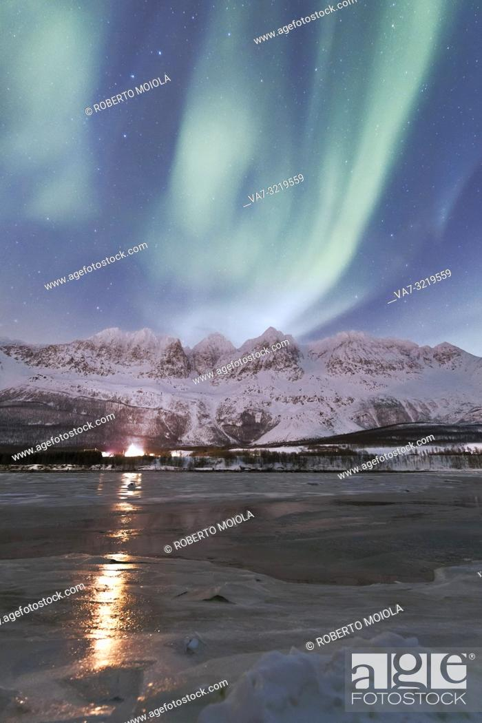 Stock Photo: The Northern Lights and starry sky reflected in the frozen sea Nordkjosbotn Lyngen Alps Tromsø Norway Europe.