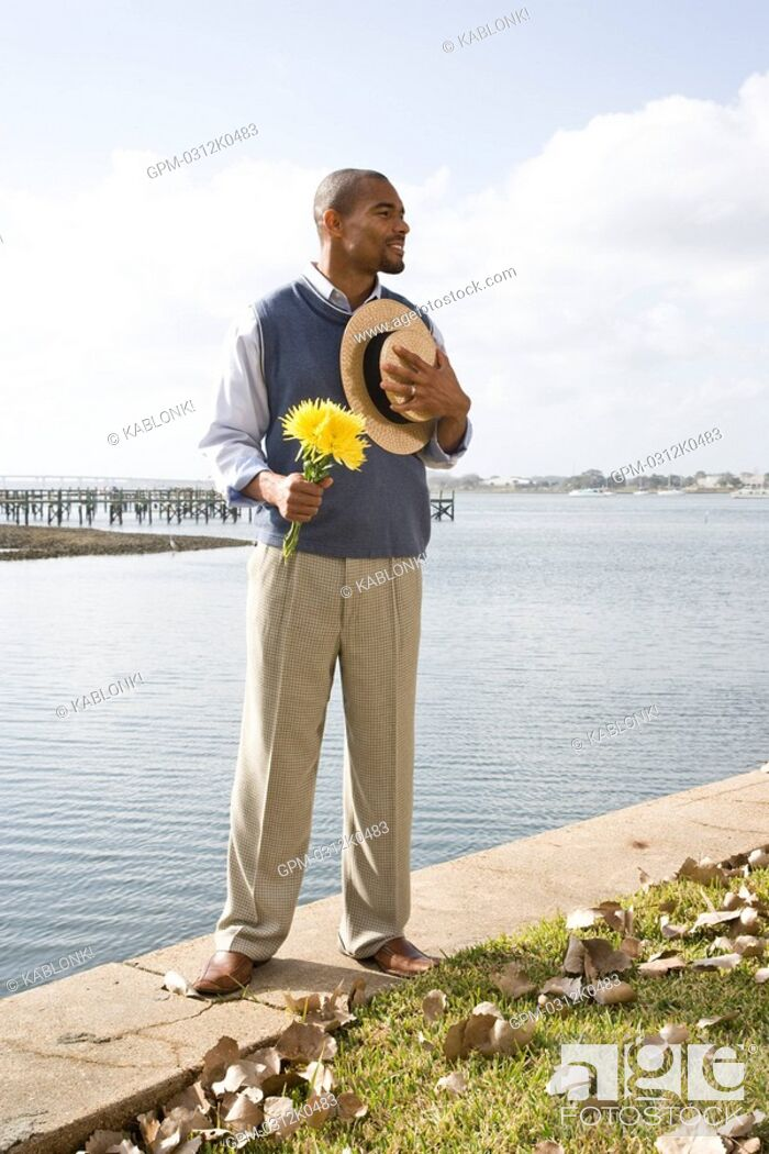 Imagen: Portrait of African American gentleman standing near water at garden party.