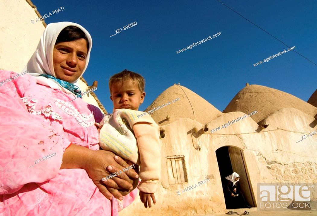 Stock Photo: Family in fronf of old traditional hive houses, Fah village near Aleppo, Syria.
