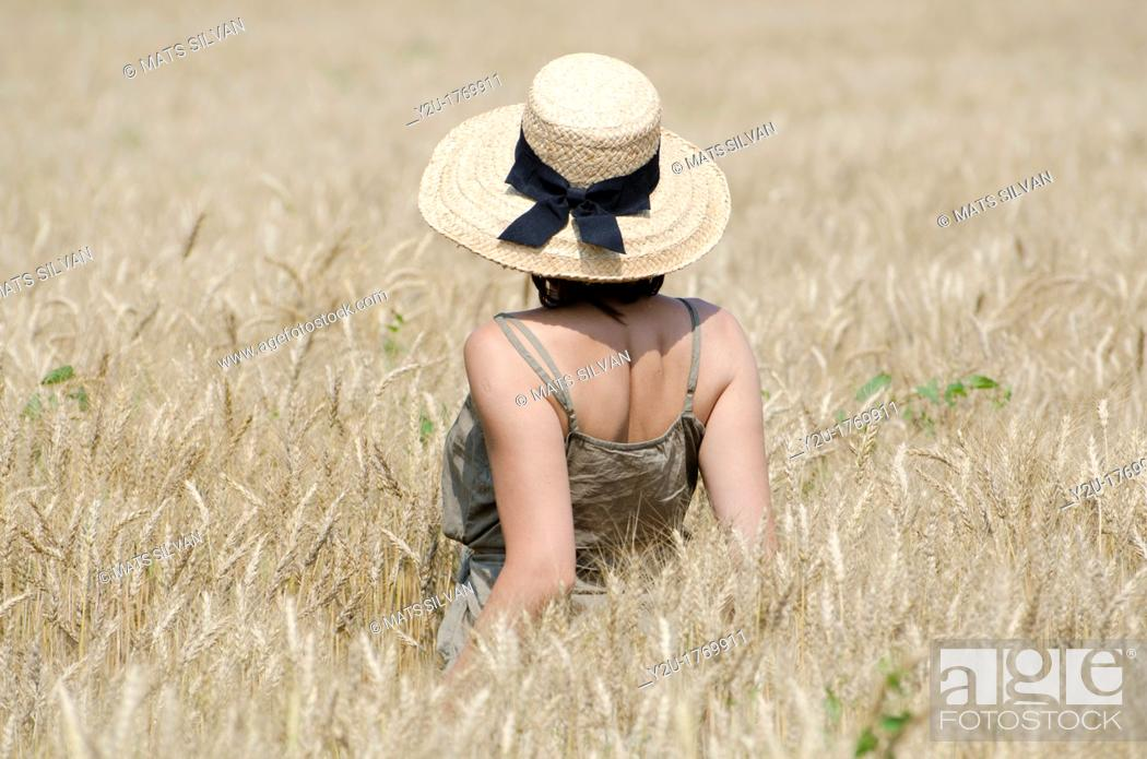 Stock Photo: Woman with a straw hat standing up in the wheat field.
