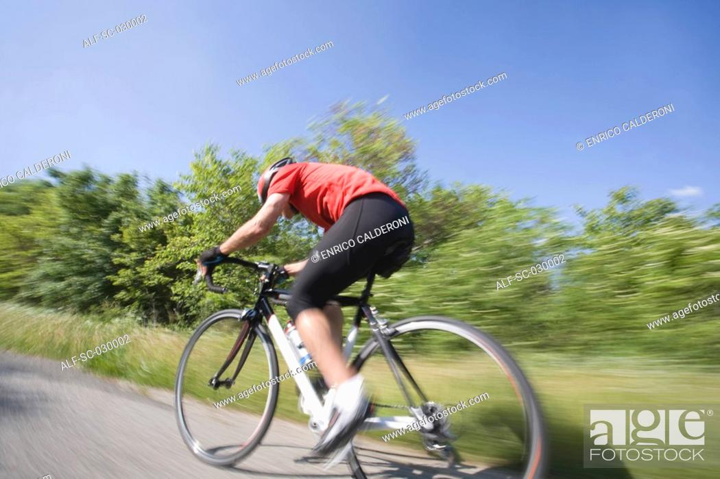 Stock Photo: Side view of a cyclist cycling on road, blurred motion.